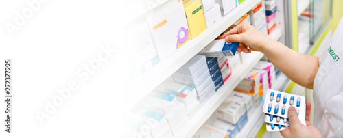 In de dag Apotheek Pharmacist holding medicine box and capsule pack in pharmacy drugstore on white background for copy space