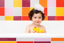 Cute Toddler In Bathtub Holding Rubber Ducks