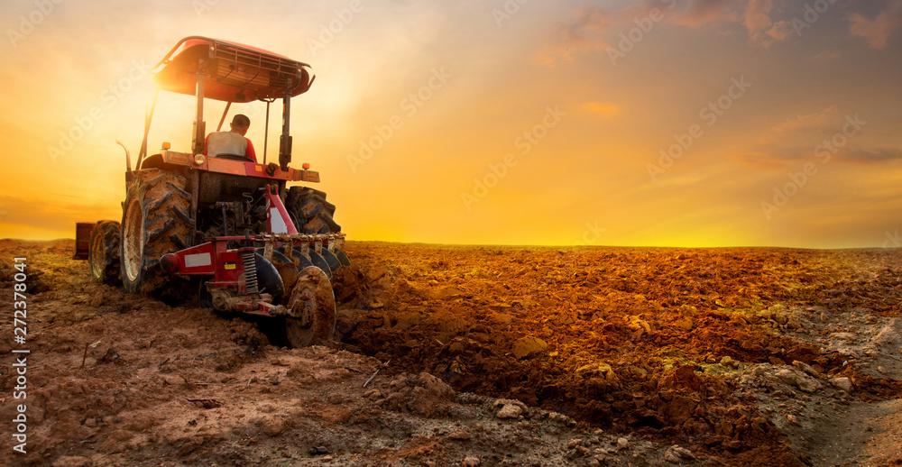 Fototapeta  tractor is preparing the soil for planting over sunset sky background