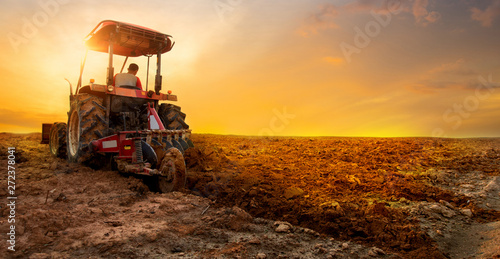 tractor is preparing the soil for planting over sunset sky background Canvas Print