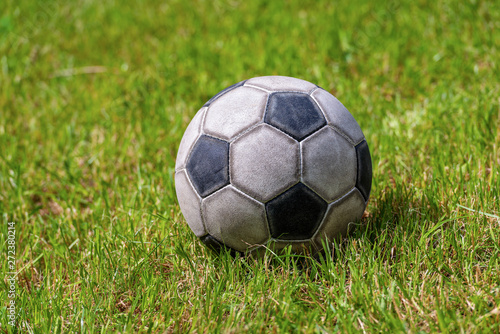 Obraz Close-up of an old leather soccer ball on green grass, football sport concept - fototapety do salonu
