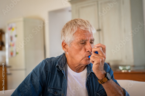 Fototapeta Senior man using asthma pump