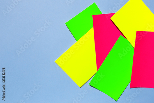 Neon colorful sticky note paper on blue background. Copy space for your text. Flat lay, top view.