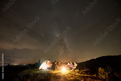 Company of five happy tourists hikers with guitar, men and women sitting by burning campfire near tent, enjoying beautiful camping night under dark starry sky with bright Milky Way.