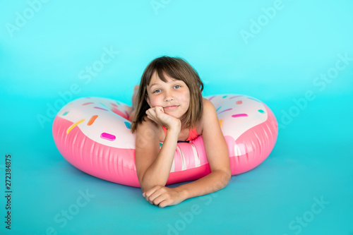 fototapeta na drzwi i meble Cute girl in blue swimsuit with huge nflated rubber ring on emerald colour background