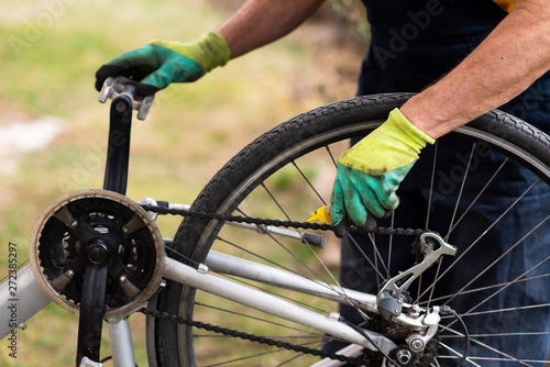 Fotomural  Man lubricating bicycle chain maintaining for the new season