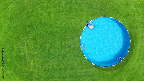 fototapeta na drzwi i meble Aerial. Metal frame pool with water on a green grass lawn. Top view. Copy space.