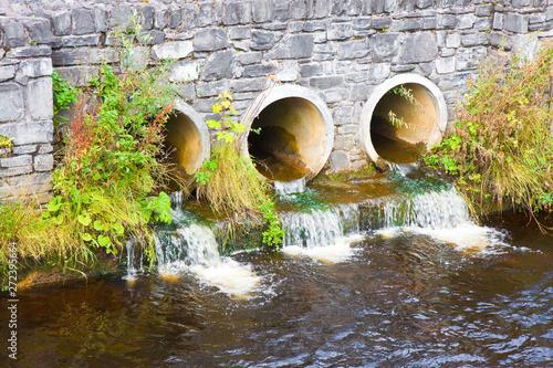 Fotografie, Tablou Toxic water running in concrete drainpipe towards the river