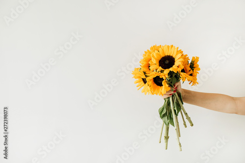 Women's hand hold yellow sunflowers bouquet on white background. Summer floral concept.