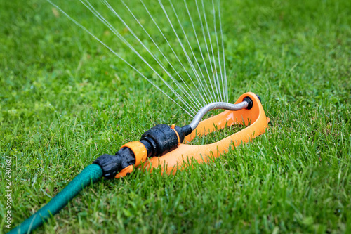 Photo lawn watering - water sprinkler working in green grass at home backyard
