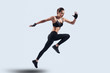 Full of energy. Full length of attractive young woman in sports clothing jumping while hovering against grey background