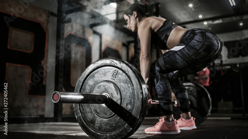 Fototapeta Sport. Muscular women lifting deadlift in the gym with barbell. Dramatic interior with smoke. obraz