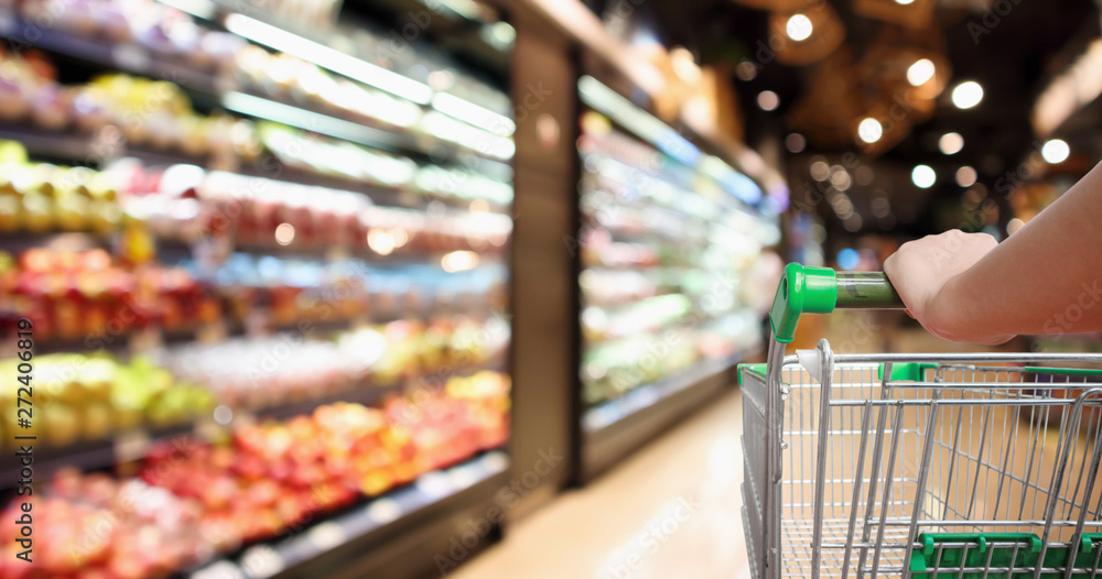 Fototapeta woman hand hold supermarket shopping cart with abstract blur organic fresh fruits and vegetable on shelves in grocery store defocused bokeh light background