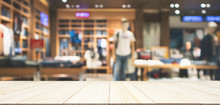 Empty Wood Table Top With Abstract Blur Clothing Store In Modern Shopping Mall Defocused Background