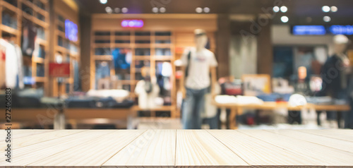 Fotomural  Empty wood table top with abstract blur clothing store in modern shopping mall d