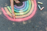 Fototapeta Tęcza - child's drawing of rainbow and colorful chalks on a street