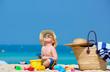 Leinwandbild Motiv Two year old toddler boy playing with beach toys on beach
