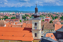 Aerial View Of Sibiu City Center With Imposing Tower Of Holy Trinity Roman Catholic Church (Biserica Romano-Catolica Sfanta Treime) In Bright Daylight. Snow On Mountains In The Far Back.