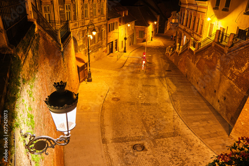 Obraz View from Liars Bridge (Podul Minciunilor) in Sibiu, Romania, at night, with beautiful, artistic, medieval-style street lamp and stairs. Popular touristic destination. - fototapety do salonu