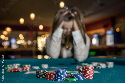 Cuadros en Lienzo Upset woman in casino sitting behind poker table