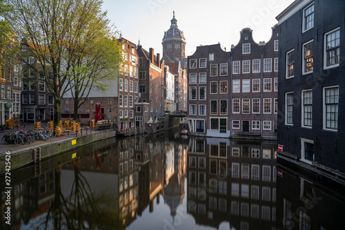 Photo  St Nicolaaskerk with canal houses in Amsterdam in the Netherlands