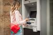 Leinwandbild Motiv Woman traveler takes out money at an ATM in Europe