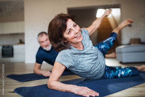 Carta da parati A senior couple indoors at home, doing exercise on the floor.