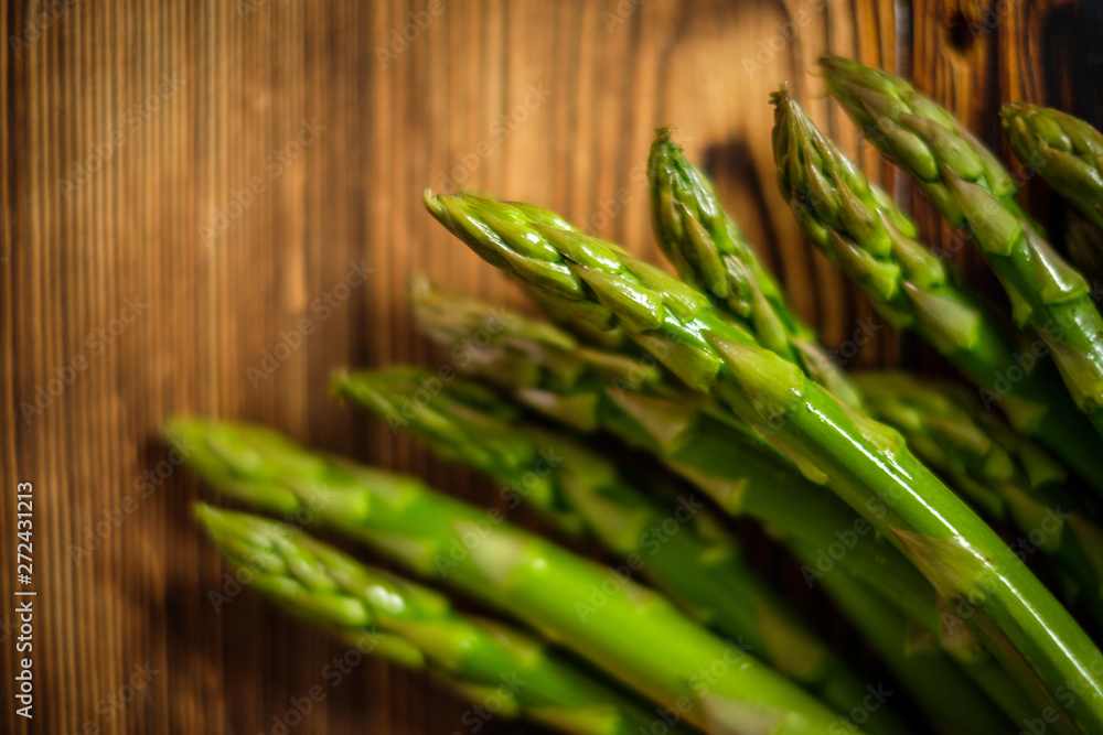 Bunch of fresh raw garden asparagus on wooden table background.