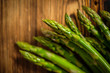 Leinwandbild Motiv Bunch of fresh raw garden asparagus on wooden table background.