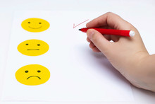 Cut Out Of Paper Mood Emoticons On A White Background. The Hand Marks The Selected Mood With A Felt Pen.