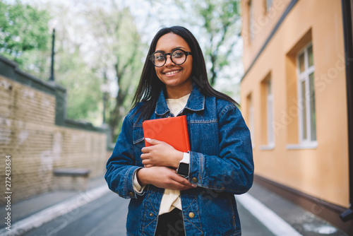 Valokuvatapetti Half length portrait of smiling afro american female student standing with favorite book outdoors in college yard