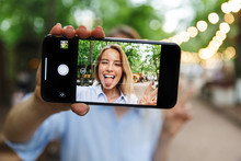 Photo Of Blonde Smiling Woman Selfie Photo On Smartphone With Sticking Out Her Tongue And Gesturing Peace Sing