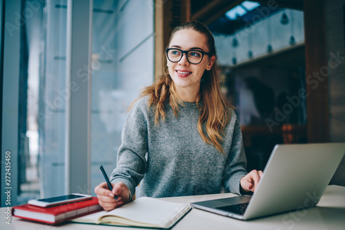 Fotografia  Positive female student spending time for learning language using laptop compute
