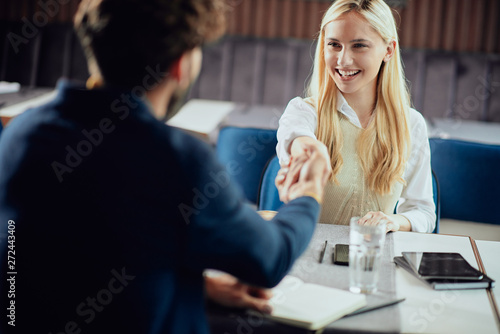 Fotografia  Two business partners shaking hands while sitting in coffee shop.