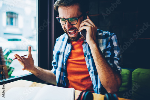 Fototapety, obrazy: Frustrated bearded young man in eyeglasses for vision correction arguing calling on smartphone device.Angry hipster guy shouting while talking on modern telephone.Annoyed male crying on cellular
