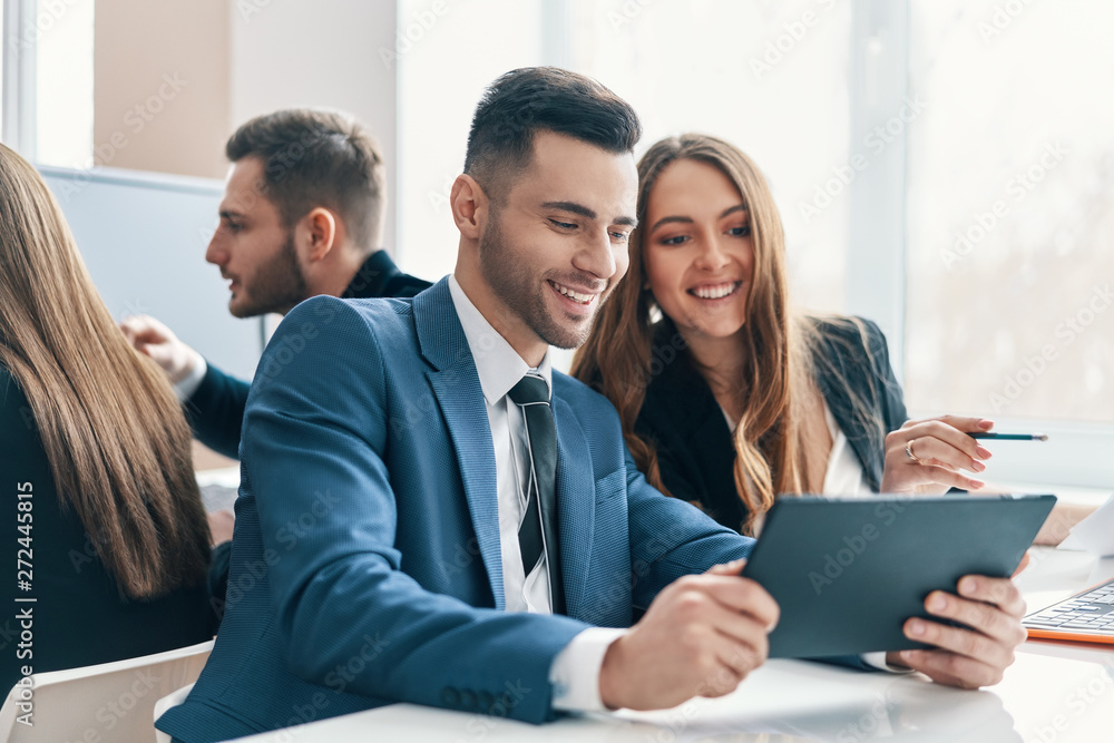 Fototapeta Smiling successful business people discussing ideas using digital tablet in office