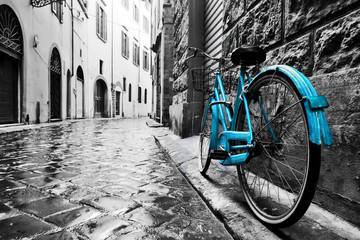 Retro blue bike on old town street.
