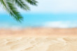 Leinwandbild Motiv Empty sand beach in front of summer sea and palm tree background with copy space