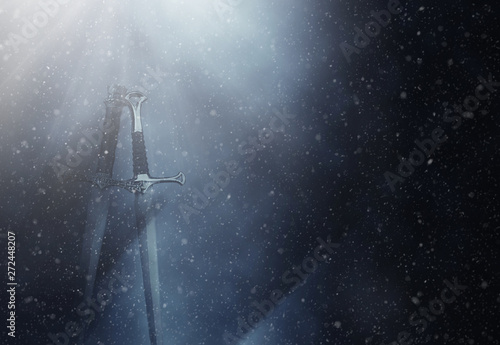 mysterious and magical photo of silver sword over gothic snowy black background Tablou Canvas
