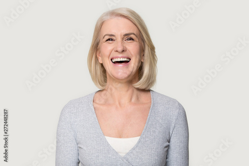 Headshot happy aged female laughing posing on grey studio background