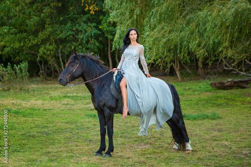 beautiful young woman in beautiful dress on black horse in nature Wallpaper Mural
