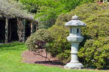 Spring Garden With Oriental Grey Stone Lantern Against Flowering Azalea Bush In An English Rural Countryside .