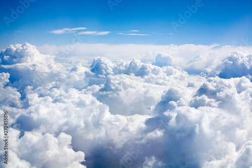 White clouds on blue sky background close up, cumulus clouds high in azure skies, beautiful aerial cloudscape view from above, sunny heaven landscape, bright cloudy sky view from airplane, copy space - 272455816