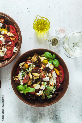 Photo Stands Asia Country Italian traditional Tuscan panzanella salad with fresh tomatoes and cheese in clay plates and white wine in a bottle and glasses . authentic Mediterranean healthy food