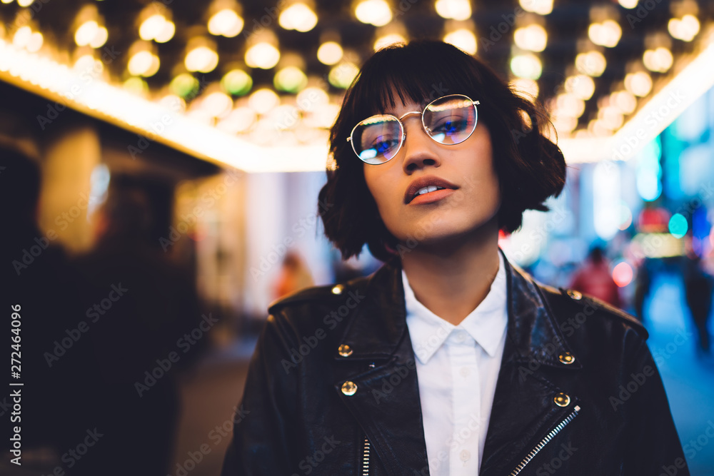 Fototapety, obrazy: Half length portrait of gorgeous brunette young woman in stylish eyeglasses looking at camera.Charming caucasian hipster girl with short haircut dressed in fashionable wear standing in night New York