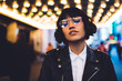 canvas print picture - Half length portrait of gorgeous brunette young woman in stylish eyeglasses looking at camera.Charming caucasian hipster girl with short haircut dressed in fashionable wear standing in night New York