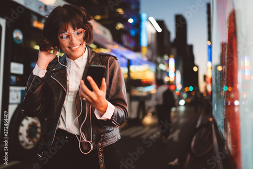 obraz PCV Cheerful pretty young woman in cool eyeglasses and trendy wear walking on metropolis street with night lights enjoying songs from playlist in earphones and reading sms with good news on smartphone