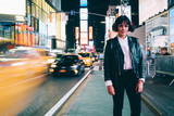 Fototapeta New York - Full length portrait of stylish caucasian hipster girl in trendy eyeglasses looking at camera while standing in urban setting of night New York city with street traffic in neon illumination and lights