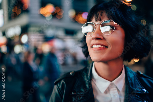 obraz PCV Charming positive brunette young woman in cool spectacles enjoying night street standing on bokeh background.Cheerful attractive hipster girl in stylish eyeglasses and leather jacket laughing