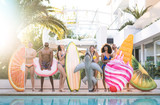 Front view of friends at swimming pool party with lilo airbed and swim wear - Youth vacation concept with happy guys and girls having fun in summer day at luxury resort - Young people on bright filter